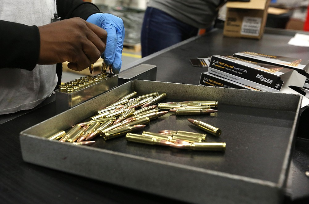 A Sig Sauer employee loads new ammunition into boxes at the company's plant in Jacksonville. (Arkansas Democrat-Gazette/Thomas Metthe)