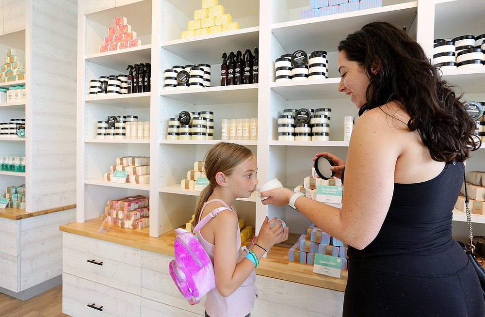 Lumen Dietrich smells a sample of lotion with her nanny Sammie Garcia at Buff City Soap on North Shiloh Drive in Fayetteville. Check out nwaonline.com/210620Daily/ and nwadg.com/photos for a photo gallery. (NWA Democrat-Gazette/David Gottschalk)