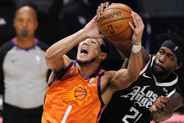 Los Angeles Clippers guard Patrick Beverley attempts to block a shot by Phoenix Suns guard Devin Booker during the first half in Game 3 of the NBA basketball Western Conference Finals on Thursday, June 24, 2021, in Los Angeles. (AP Photo/Mark J. Terrill)