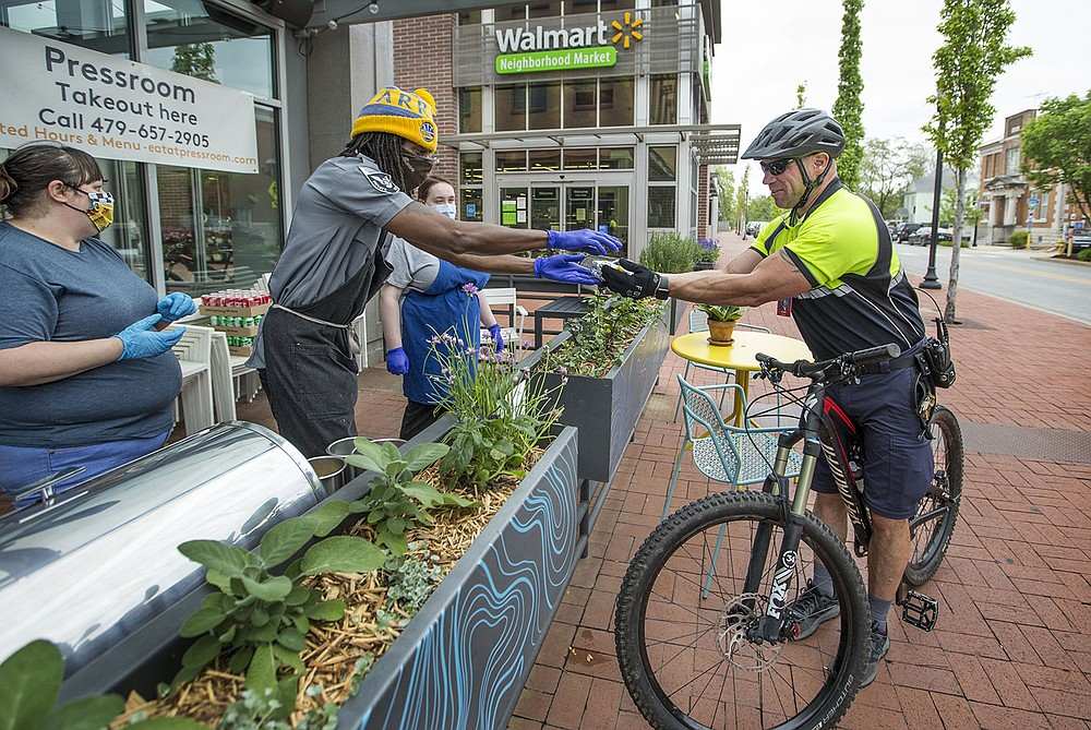 Luke Bullard (right) with Walmart corporate security is served by Lillie Lindsey, Jason Lofton and Erika Alawdi of popular downtown Bentonville restaurant Pressroom on April 28, 2020, a day honoring essential workers by handing out free hot dogs and sodas. (NWA Democrat-Gazette/Ben Goff)
