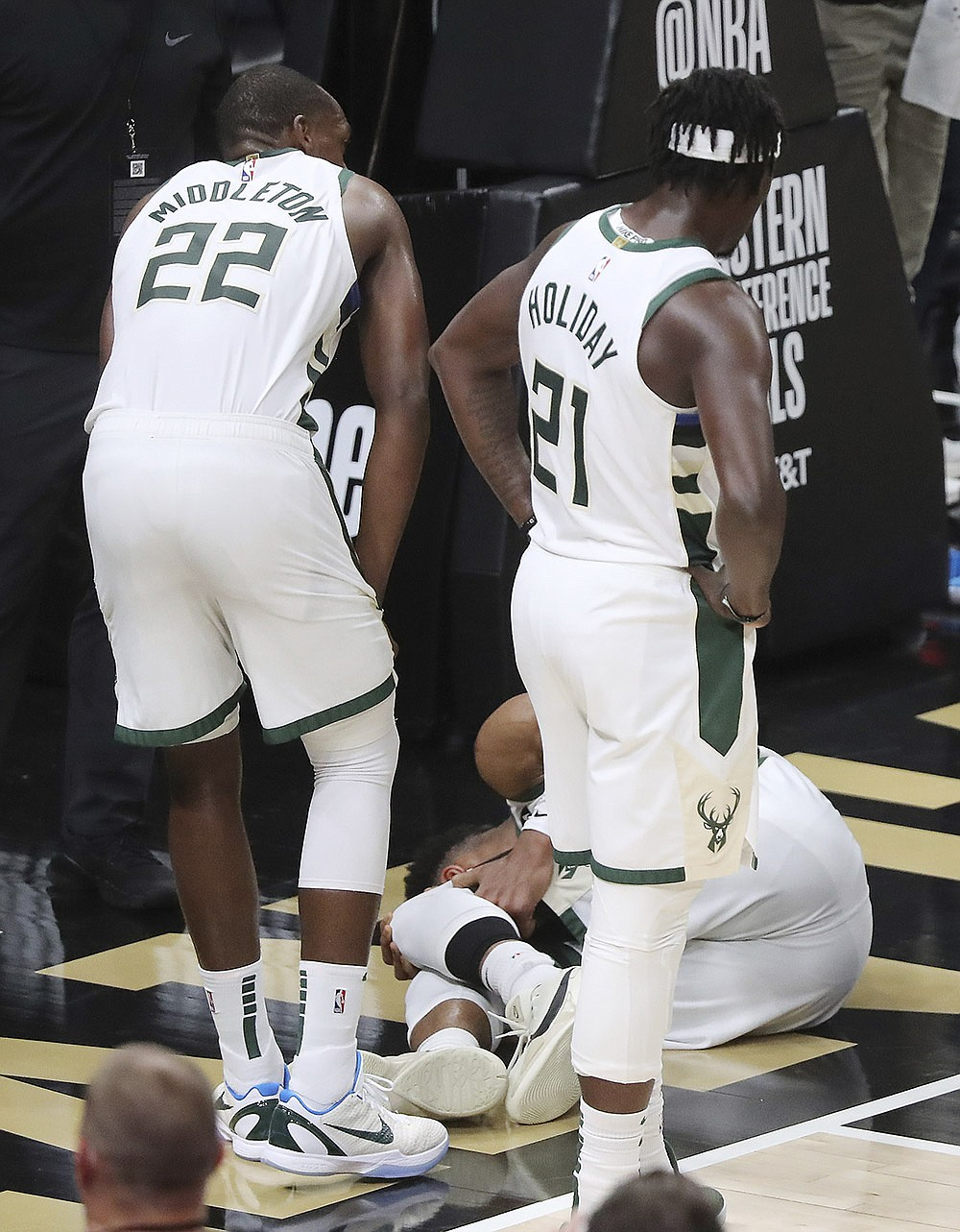 Milwaukee Bucks teammates Khris Middleton (left) and Jrue Holiday look at Giannis Antetokounmpo after he was injured during the second half in Game 4 of the NBA Eastern Conference finals on Tuesday. Antetokounmpo is doubtful tonight for Game 5 with a hyperextension of his left knee. (AP/Curtis Compton/Atlanta Journal-Constitution)