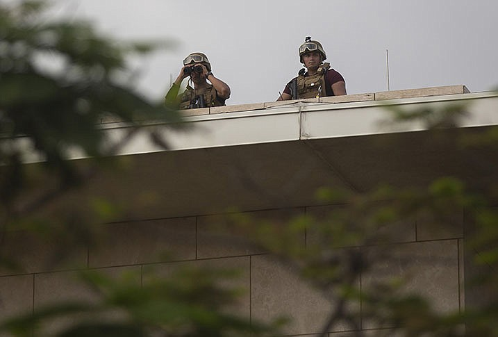 U.S. soldiers stand guard Friday on the roof of the U.S. Embassy in Port-au-Prince, Haiti, as a large crowd gathers outside. (AP/Joseph Odelyn)