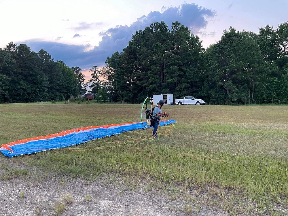 """Don Guthrie prepares to take off into flight on his powered paraglider on Monday, July 5. He calls the process, which requires a running start before the motor and wind combine to life him into the air, """"running into the skies."""" (Courtesy of Johnathan Estes)"""