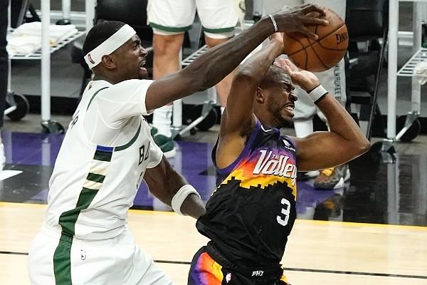 Milwaukee Bucks center Bobby Portis, left, defends Phoenix Suns guard Chris Paul (3) during the second half of Game 5 of the NBA Finals on Saturday, July 17, 2021, in Phoenix. (AP Photo/Matt York)