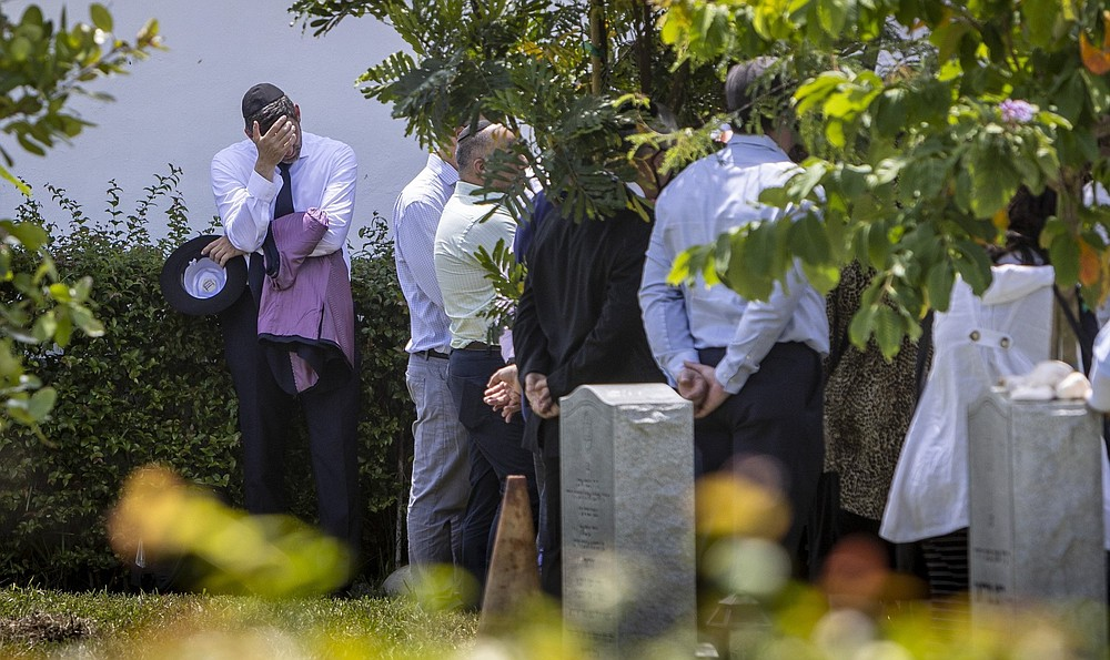 A man pauses as friends and relatives gather Monday around the grave site of Brad Cohen at Mt. Sinai Memorial Park in Opa-locka, Fla. Cohen died in the condo collapse. (AP/Miami Herald/Jose A Iglesias)