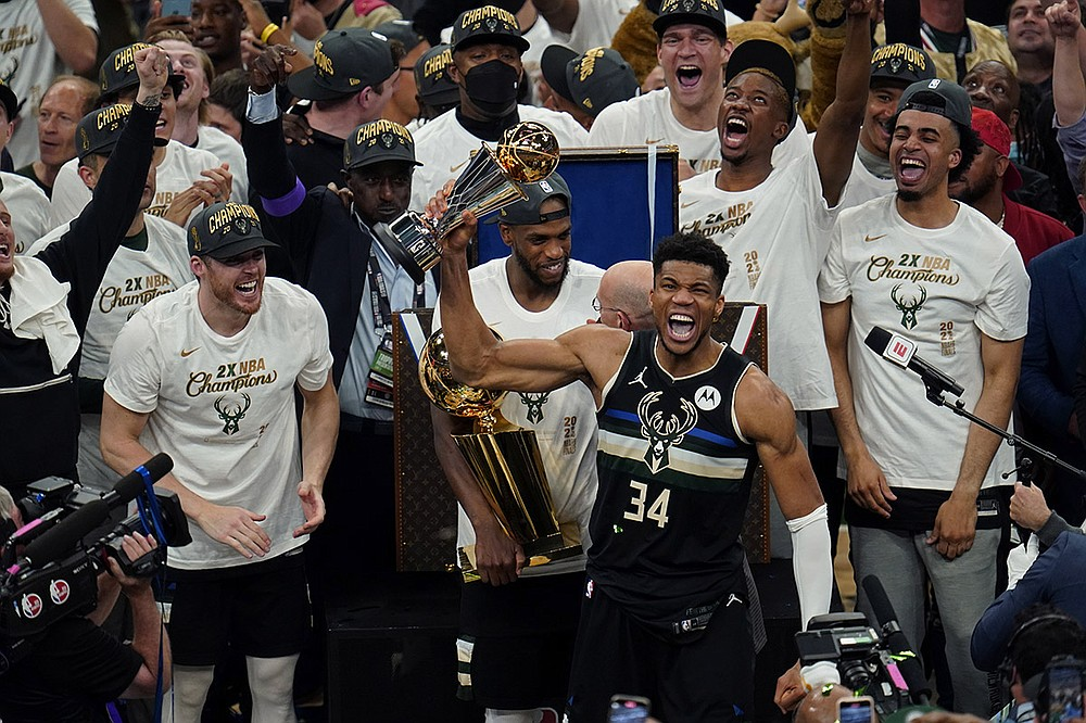 Milwaukee's Giannis Antetokounmpo celebrates with his NBA Finals MVP trophy Tuesday night after the Bucks defeated the Phoenix Suns in Game 6 for the championship. Antetokounmpo scored at least 40 points in three of the six NBA Finals games, including 50 in the series-clincher. (AP/Paul Sancya)