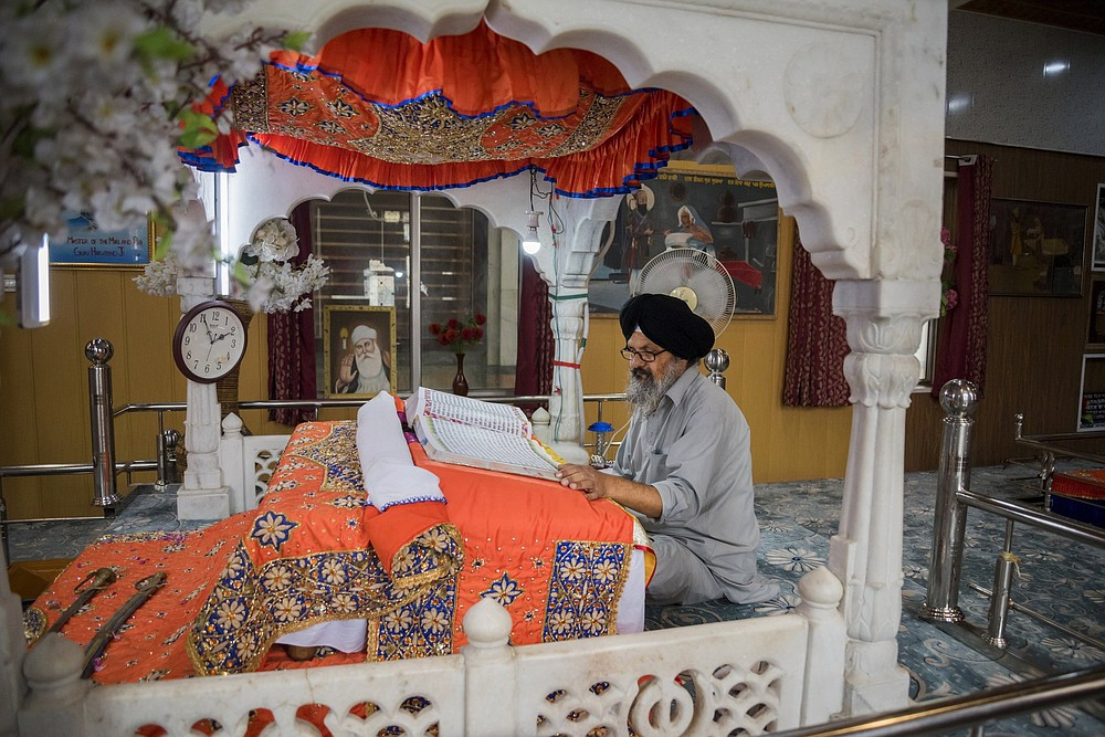 A man reads from a book of religious scripture inside the Srinagar, India-based Chatti Padshahi, a Sikh place of worship, called a gurudwara. (The New York Times/Showkat Nanda)