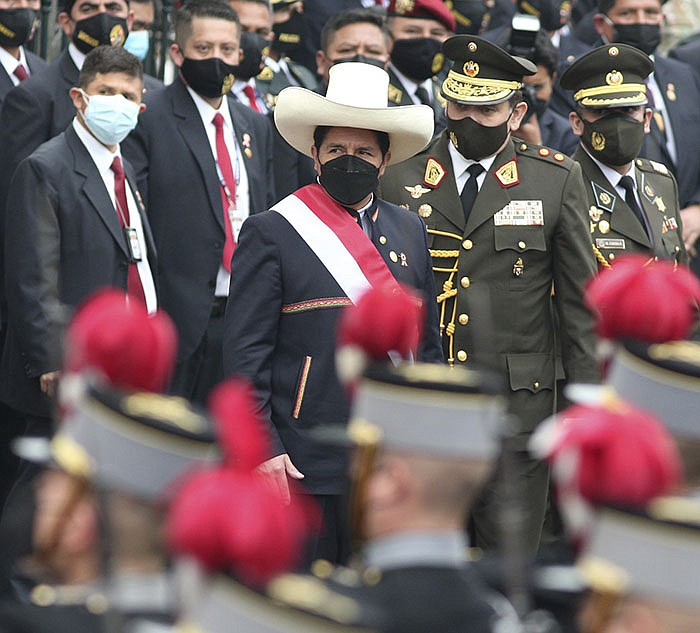 Peru's newly sworn-in President Pedro Castillo (center) leaves Congress during inauguration ceremonies Wednesday in Lima. The leftist political novice Castillo, a rural teacher who succeeds appointed President Francisco Sagasti, is the country's first president of peasant origin. His promise to be a champion of the poor will be tested with lawmakers who are deeply divided. (AP/Francisco Rodriguez)