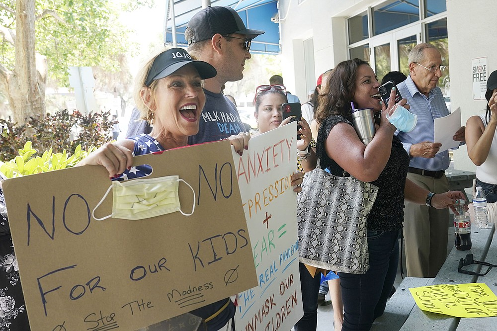 Joann Marcus (left) cheers Wednesday at an emergency meeting of the Broward School Board in Fort Lauderdale, Fla. A small but vocal group spoke vehemently against masks, saying their personal rights were being eroded and their children were suffering socially. Some protesters burned masks outside the building. (AP/Marta Lavandier)