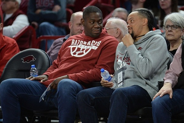 Former Fayetteville High School and Arkansas standouts Ronnie Brewer (left) and Wallace Spearmon speak Saturday, Jan. 25, 2020, during the Razorbacks' game with TCU in Bud Walton Arena.