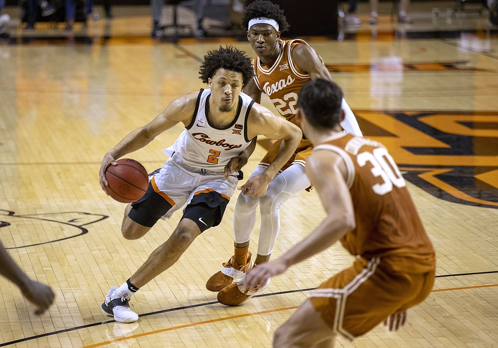 FILE - In this Feb. 6, 2021, file photo, Oklahoma State guard Cade Cunningham (2) drives past Texas forward Kai Jones (22) and Brock Cunningham (30) during the first overtime of the NCAA college basketball in Stillwater, Okla.  (AP Photo/Mitch Alcala, File)