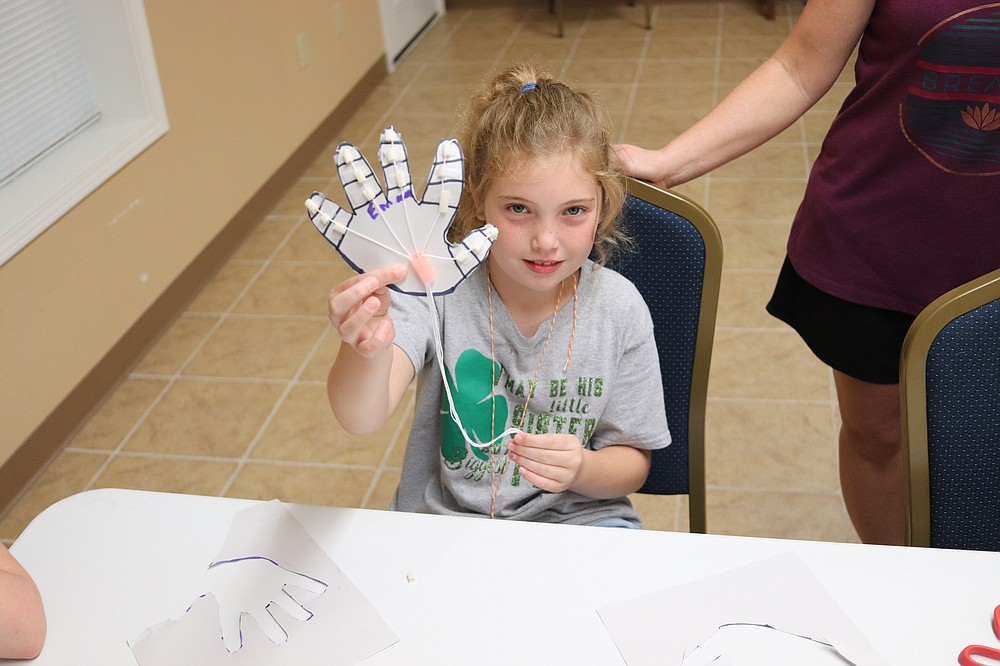 Cub Scout Emma was one of the first to finish her hand and wasted no time in showing it off. (Matt Hutcheson/News-Times)