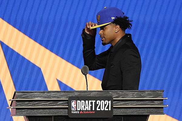 Moses Moody poses walks off the stage after being selected 14th overall by the Golden State Warriors during the NBA basketball draft, Thursday, July 29, 2021, in New York. (AP Photo/Corey Sipkin)