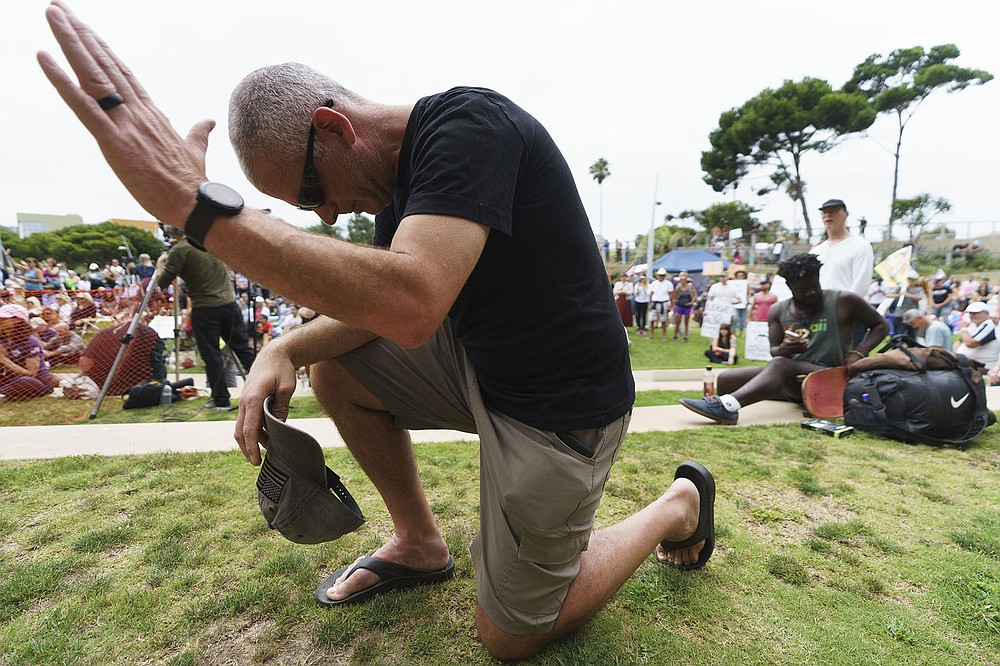 """Steve Taylor, a U.S. Army chaplain, prays Saturday at a """"S.O.S California No Vaccine Passport Rally"""" at Tongva Park in Santa Monica, Calif., protesting Los Angeles' impending vaccine mandate. (AP/Damian Dovarganes)"""