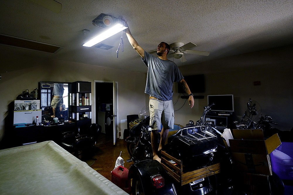 Donnie Pearson adjusts a light at his home Wednesday after power was restored to his neighborhood in New Orleans. Most of New Orleans remains without power, along with much of south Louisiana. (AP/Eric Gay)