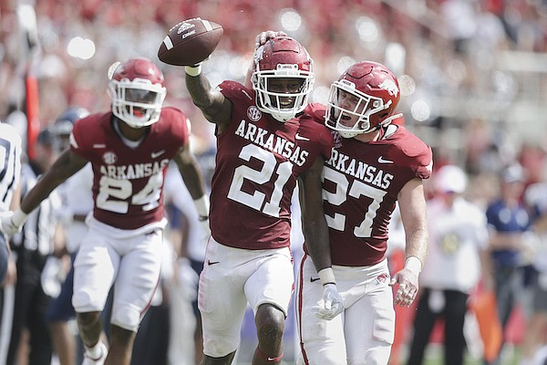 Arkansas cornerback Montaric Brown (21) celebrates with linebacker Hayden Henry (27) after intercepting a pass during the fourth quarter of a game against Rice on Saturday, Sept. 4, 2021, in Fayetteville.