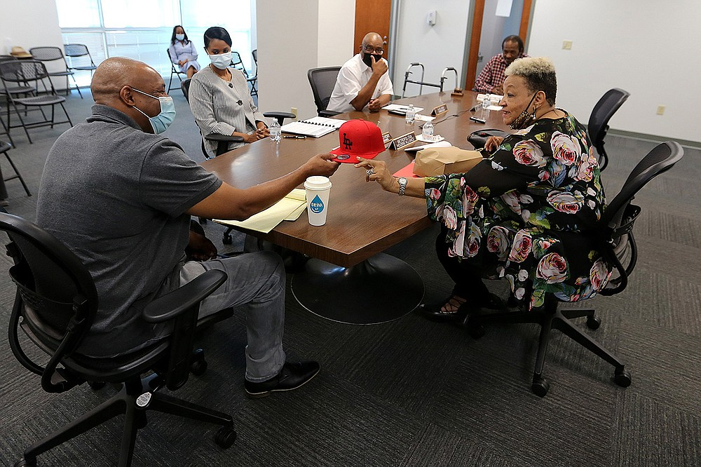 Metropolitan Housing Alliance board member Leta Anthony (right) gives a Little Rock hat to outgoing interim executive director Andy Delaney during the MHA board meeting on Thursday in Little Rock. (Arkansas Democrat-Gazette/Thomas Metthe)