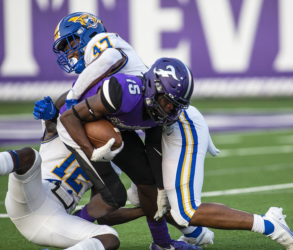 Ryan Maxwell (15) of Fayetteville gets tackled by Thower and Donnell Packer. More photos at arkansasonline.com/911nlrfhs/ (Special to NWA Democrat-Gazette/David Beach)