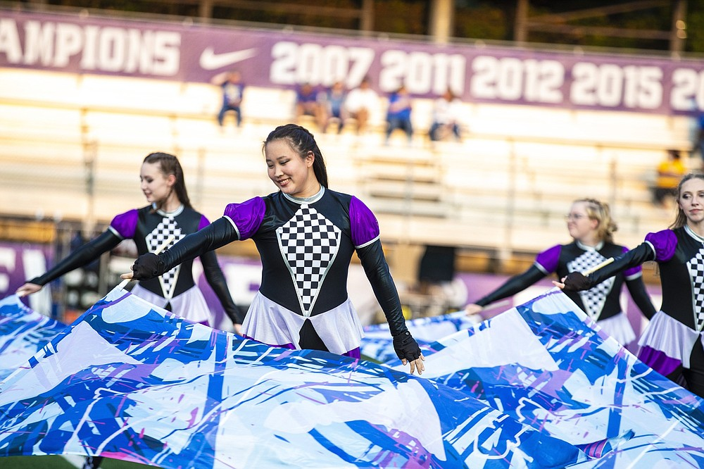Members of the Fayetteville flag team perform Friday during the Bulldogs' 14-7 loss to the North Little Rock Charging Wildcats at Harmon Field in Fayetteville. (Special to the NWA Democrat-Gazette/David Beach)