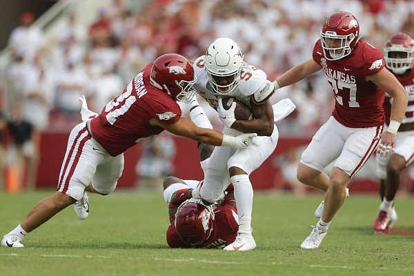 Arkansas safety Joe Foucha (ground) and linebacker Grant Morgan (31) stop Texas running back Bijan Robinson (5) on Saturday, Sept. 11, 2021 during the first quarter of a football game at Reynolds Razorback Stadium in Fayetteville.