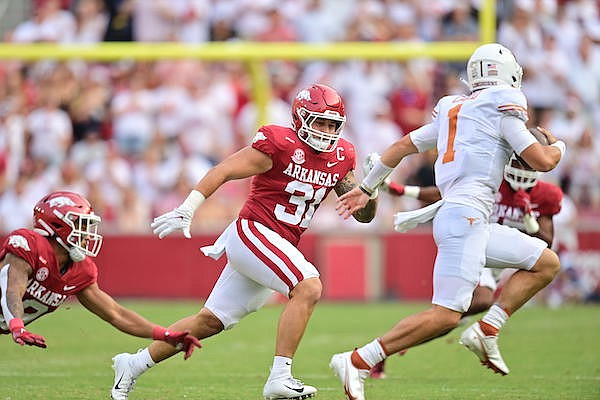Arkansas linebacker Grant Morgan (31) chases Texas quarterback Hudson Card during a game Saturday, Sept. 11, 2021, in Fayetteville.