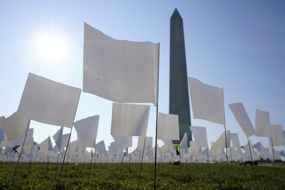 """Flags representing Americans whose lives have been lost to covid-19 are placed on the National Mall near the Washington Monument on Wednesday. The flags, which will number more than 630,000 when all are placed, are part of artist Suzanne Brennan Firstenberg's temporary art installation, """"In America: Remember."""" (AP/Patrick Semansky)"""