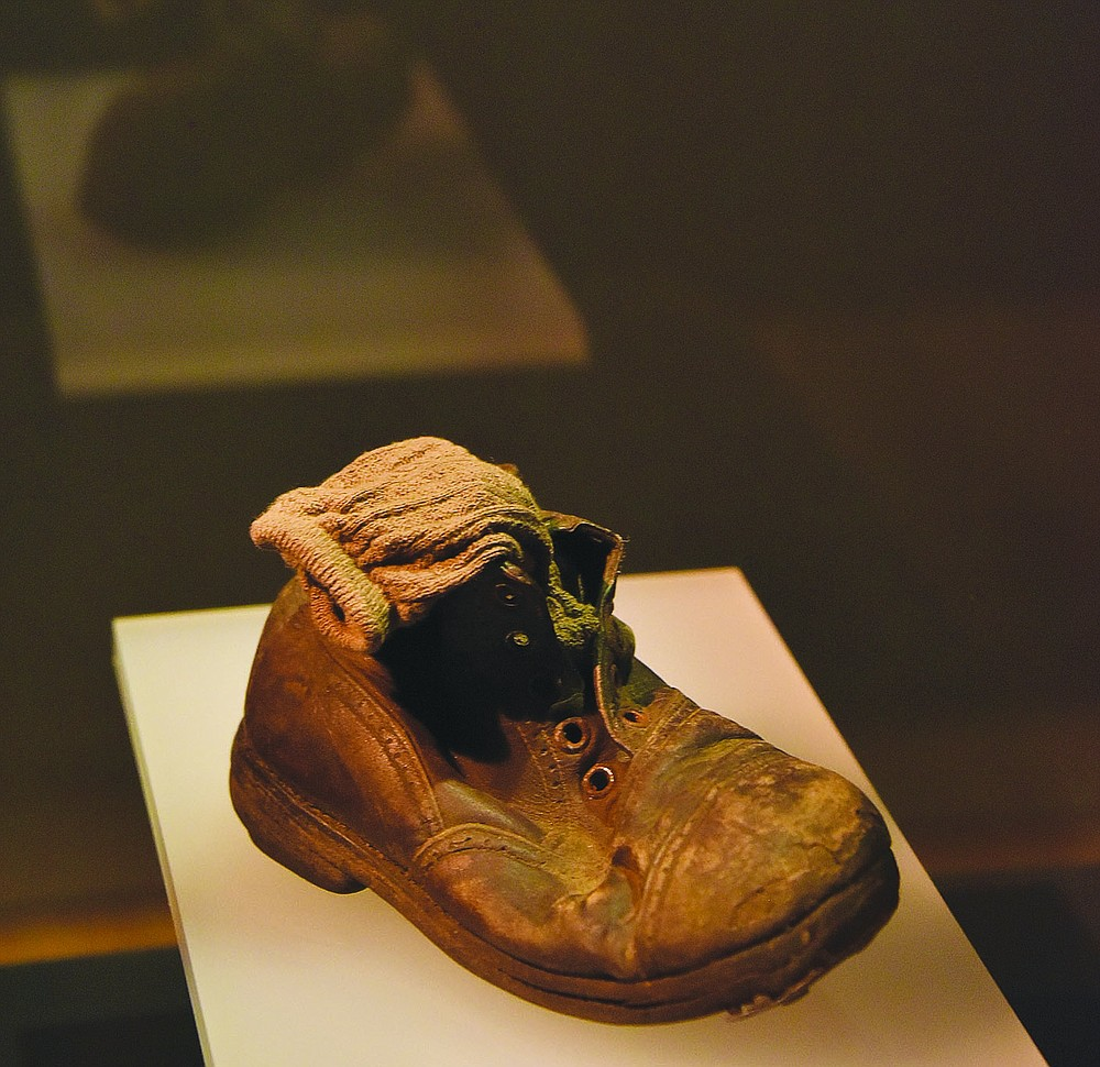 """Many visitors to the """"Auschwitz. Not long ago. Not far away"""" exhibit currently open at Union Station in Kansas City, Mo., talk about a single little shoe, with a tiny sock tucked neatly inside it, as the most poignant artifact of the World War II death camp, imagining a child expecting to put his shoes back on after a """"shower."""" (Pawel Sawicki, Auschwitz Memorial)"""