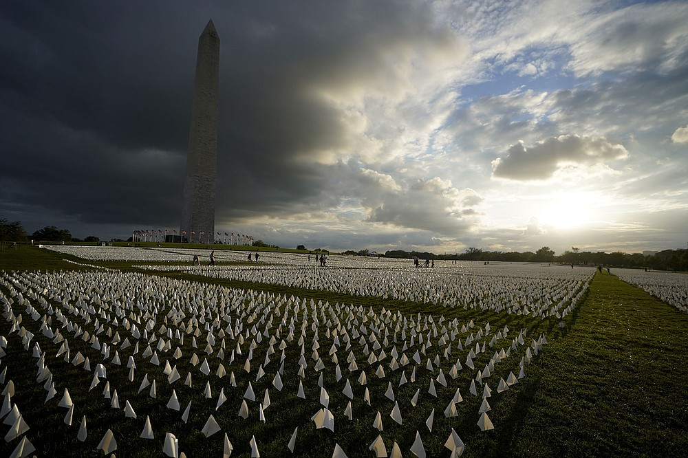 """Clouds darken the Washington Monument on Friday as people walk among white flags that are part of artist Suzanne Brennan Firstenberg's temporary art installation, """"In America: Remember,"""" on the National Mall. The installation consists of more than 630,000 flags in remembrance of Americans who have died as a result of covid-19. (AP/Brynn Anderson)"""
