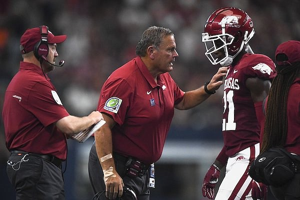 Arkansas coach Sam Pittman (center) speaks with cornerback Montaric Brown (21) during a game against Texas A&M on Saturday, Sept. 25, 2021, in Arlington, Texas.