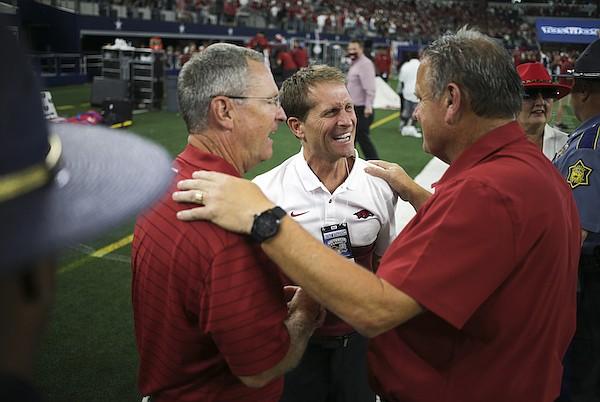 Arkansas baseball coach Dave Van Horn (left) and basketball coach Eric Musselman (center) congratulate football coach Sam Pittman following a 20-10 win over Texas A&M on Saturday, Sept. 25, 2021, in Arlington, Texas.