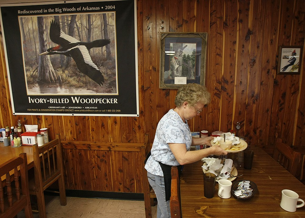 Waitress Virginia Wilhoite clears a table at Gene's Restaurant and Barbeque in Brinkley in 2009. Even though business had slowed, a painting of an ivory-billed woodpecker still held a prominent spot several years after the woodpecker spurred a flurry of tourism. (Arkansas Democrat-Gazette/Staton Breidenthal)