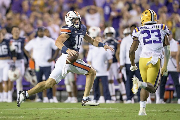 Auburn quarterback Bo Nix (10) avoids a tackle before throwing a touchdown against LSU in the first half during an NCAA football game on Saturday, Oct. 2, 2021, in Baton Rouge, La. (AP Photo/Matthew Hinton)