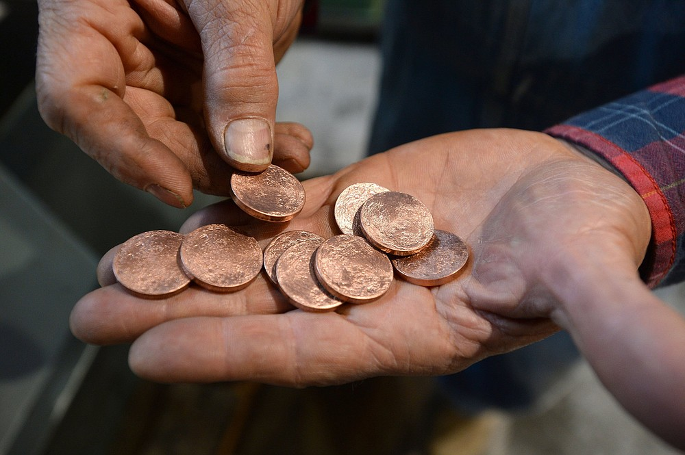 Tom Maringer of Shire Post Mint shows off a handful of newly minted coins at the company's new facility in West Fork. The local company has contracts to make collectible coins for various book, TV and film franchises. Visit nwaonline.com/210925Daily/ for today's photo gallery. (NWA Democrat-Gazette/Andy Shupe)