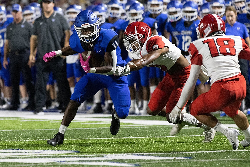 Conway's Boogie Carr (left) runs away from Cabot's Jadyn Whaley (middle) during Friday's victory in Conway. (Arkansas Democrat-Gazette/Justin Cunningham)