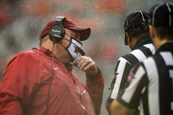 Arkansas head coach Sam Pittman talks with a game official during the first quarter of an NCAA college football game against Auburn on Saturday, Oct. 10, 2020, in Auburn, Ala. (AP Photo/Butch Dill)
