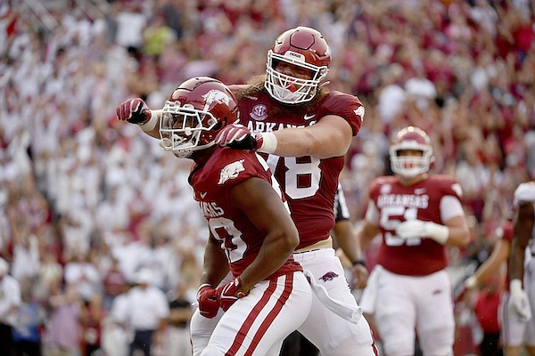 Arkansas running back Dominique Johnson (20) celebrates with Dalton Wagner (78) after scoring a touchdown against Texas during the first half of an NCAA college football game Saturday, Sept. 11, 2021, in Fayetteville. (AP Photo/Michael Woods)