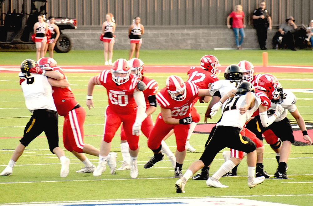 """MARK HUMPHREY  ENTERPRISE-LEADER/Farmington's offensive line creates a wall during a running play. The Cardinals throttled rival Prairie Grove, 56-27, in the annual """"Battle of 62"""" football contest played Friday before a packed house at Cardinal Stadium."""
