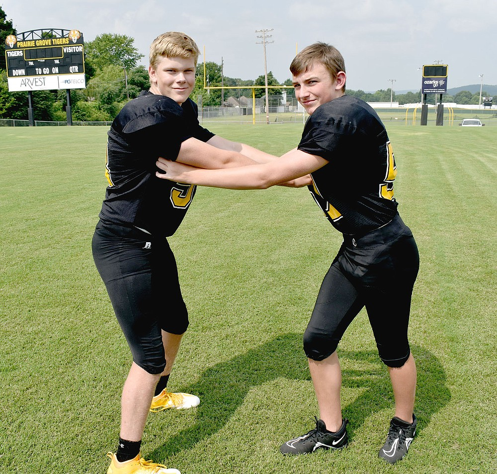 MARK HUMPHREY  ENTERPRISE-LEADER/Prairie Grove teammates Kaden Rochier (left), 5 feet 11, 184 pounds, who plays right guard for the Junior Tigers, contends with Morgan Cobb, 5 feet 10, 150 pounds, who plays linebacker during a media day football photo shoot on Aug. 4. By the time Thursday rolled around the Junior Tigers were weary of banging on each other in practice and more then willing to tango with their U.S. 62 rivals, Farmington.