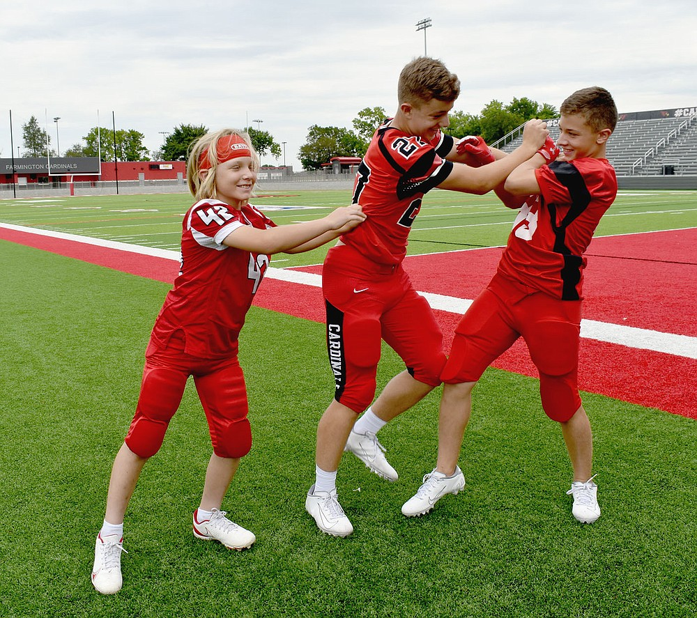 MARK HUMPHREY  ENTERPRISE-LEADER/Farmington ninth grader Zane Schmitt (No. 27, 5 feet 11 inches, 175 pounds) who plays linebacker and tight end for the Junior Cardinals, gets his strength tested by his younger brothers, Mason (No. 42, 4 feet 10 inches, 95 pounds) who plays linebacker and tight end for the pee wee team,  and Crosby (No. 33, 5 feet 5 inches, 135 pounds), who plays runningback and linebacker for the seventh grade team. The trio are the sons of Steven and Kristen Schmitt. Last week the brothers found opportunity to try out their muscles on somebody else when facing U.S. 62 rival Prairie Grove in the annual 'Battle of 62' al all football levels.