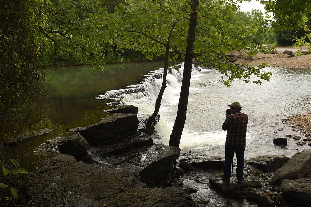 Terry Stanfill of the Decatur area takes in the sights and sounds of the Natural Dam waterfall. (NWA Democrat-Gazette/Flip Putthoff)