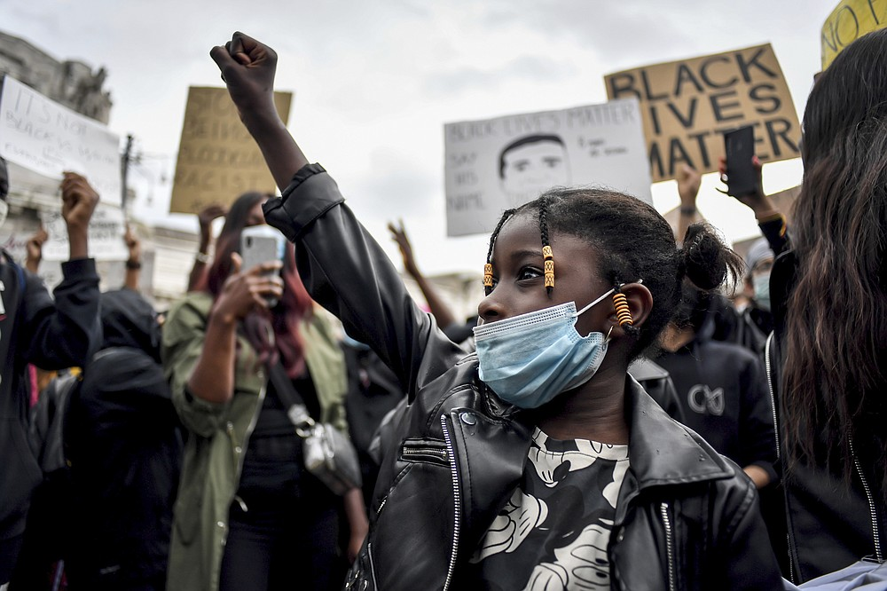 A girl clinches her fist as people gather to honor George Floyd, who died May 25 after being restrained by police in Minneapolis, USA, in Milan, Italy, Sunday, June 7, 2020. In Italy's financial capital, Milan, a few thousand protesters gathered in a square outside the central train station Sunday afternoon to demonstrate against racism. (Claudio Furlan/LaPresse via AP)
