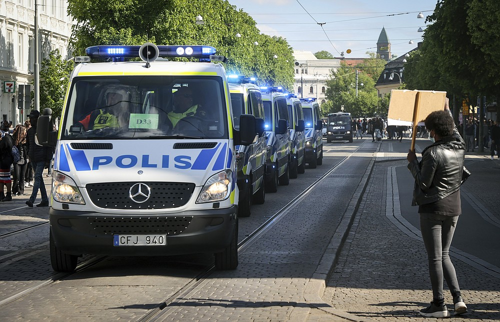 A protester holds the placard in front of police vans, during a demonstration organised to show solidarity with the Black Lives Matter movement, in Gothenburg, Sweden, Sunday, June 7, 2020. in response to the recent killing of George Floyd by police officers in Minneapolis, USA, that has led to protests in many countries and across the US. (Adam Ihse/TT News Agency via AP)