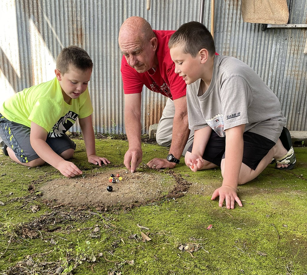 Gene Kinsey of Scott teaches Sawyer and Colin Kinsey to play marbles in June 2020. (Special to the Democrat-Gazette/Jerry Butler)