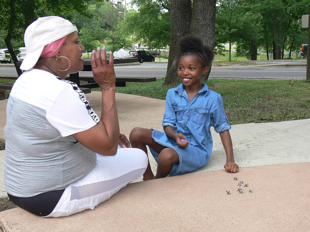Tina Willis (left) of Hot Springs congratulates her granddaughter Syncere for being quick to learn to play jacks at Hollywood Park in Hot Springs. (Special to the Democrat-Gazette/Jerry Butler)