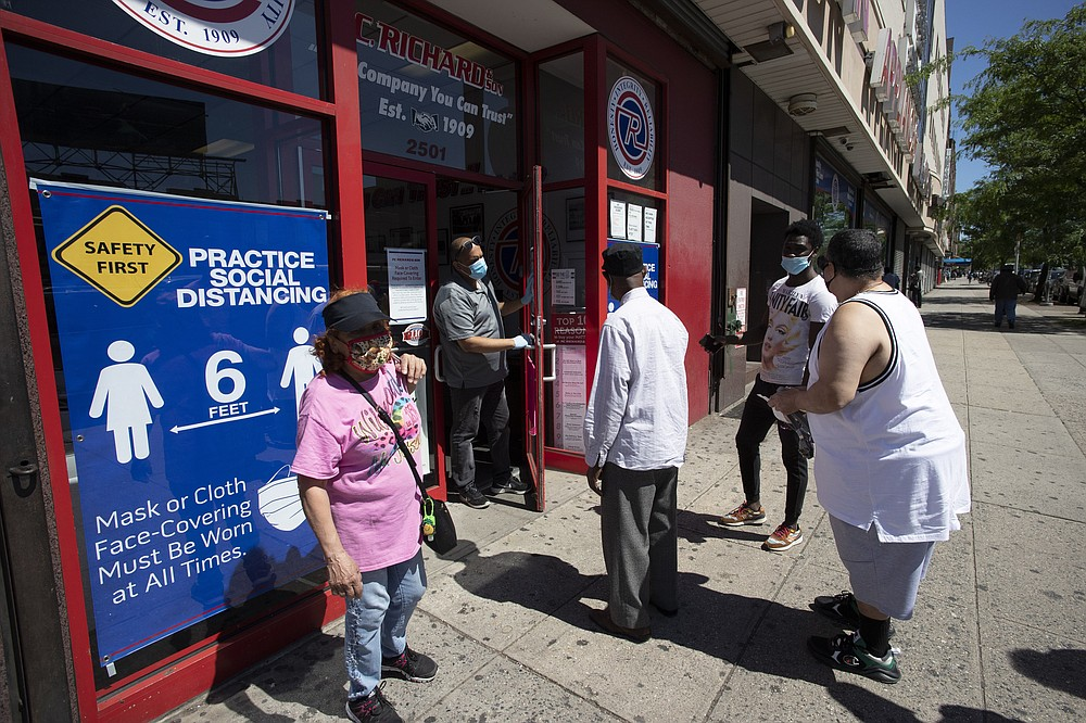 A store employee, second from left, talks to waiting customers at P.C. Richard and Son electronics and appliance store, Monday, June 8, 2020, in the Bronx borough of New York. The store is only providing pick-up orders on Monday. It will reopen its doors later in the week. After three bleak months, New York City will try to turn a page when it begins reopening Monday after getting hit first by the coronavirus, then an outpouring of rage over racism and police brutality. (AP Photo/Mark Lennihan)