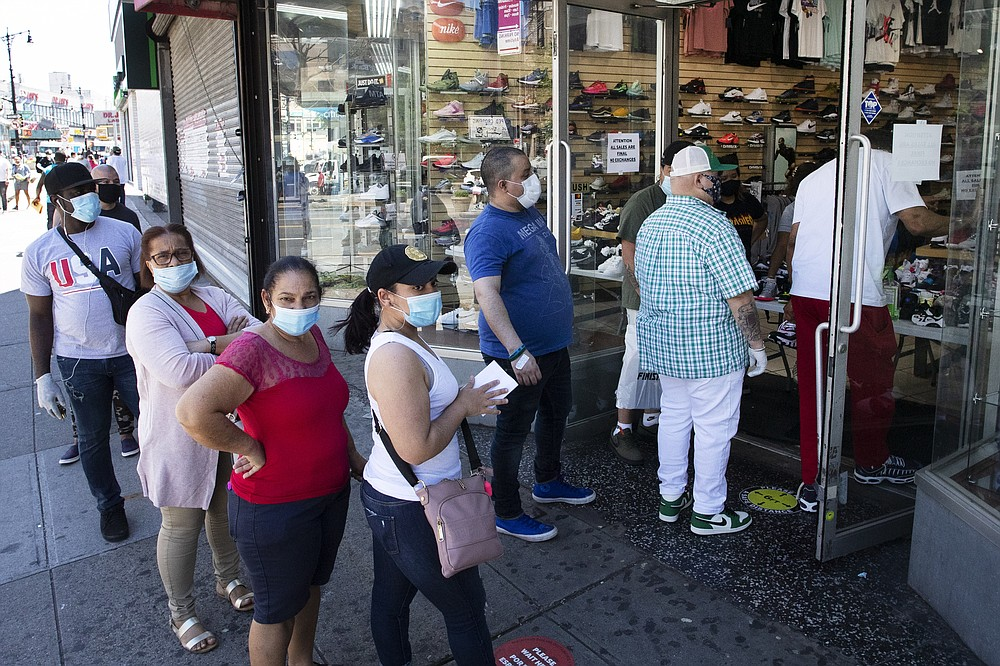 People with their face masks stand in line to enter a Sneaker Box after it reopens, Monday, June 8, 2020, in the Bronx borough of New York. After three bleak months, New York City will try to turn a page when it begins reopening Monday after getting hit first by the coronavirus, then an outpouring of rage over racism and police brutality. (AP Photo/Mark Lennihan)