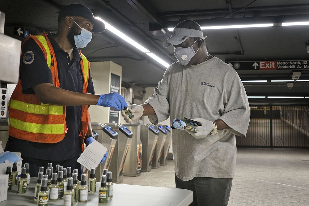 MTA employee Shawn Turner, left, gives away masks and hand sanitizer at the entrance to a subway station in New York, Monday, June 8, 2020. After three months of a coronavirus crisis followed by protests and unrest, New York City is trying to turn a page when a limited range of industries reopen Monday. (AP Photo/Seth Wenig)