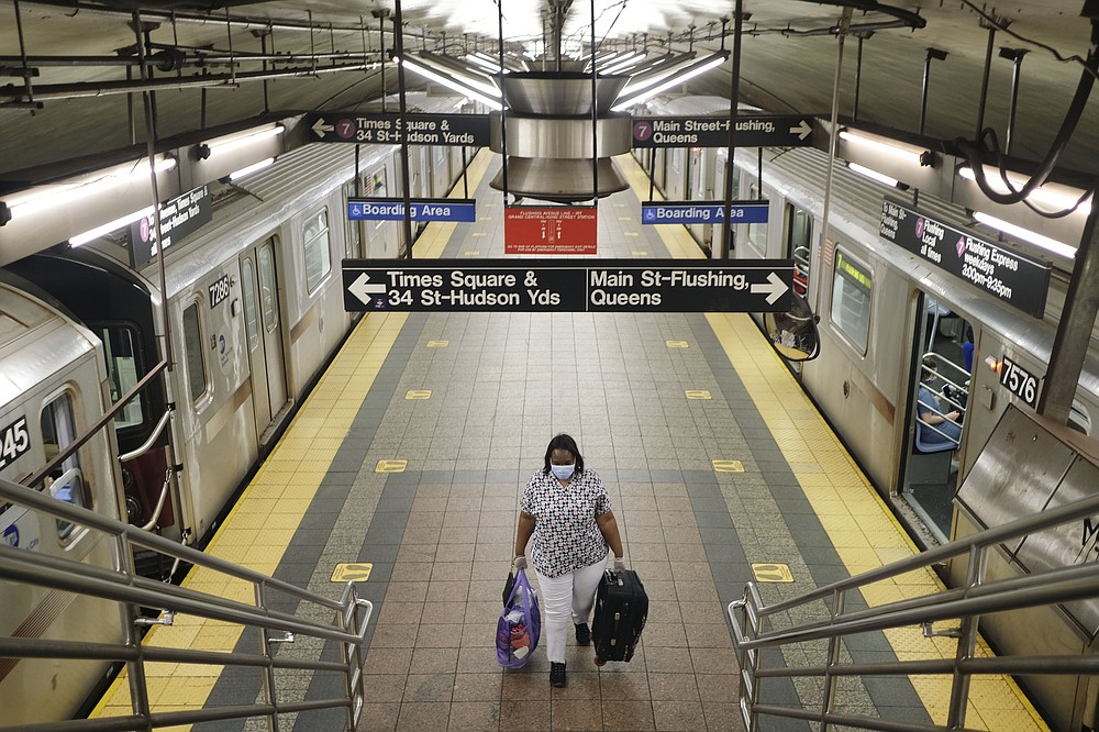 A commuters walks on a nearly empty subway platform in New York, Monday, June 8, 2020. After three months of a coronavirus crisis followed by protests and unrest, New York City is trying to turn a page when a limited range of industries reopen Monday. (AP Photo/Seth Wenig)