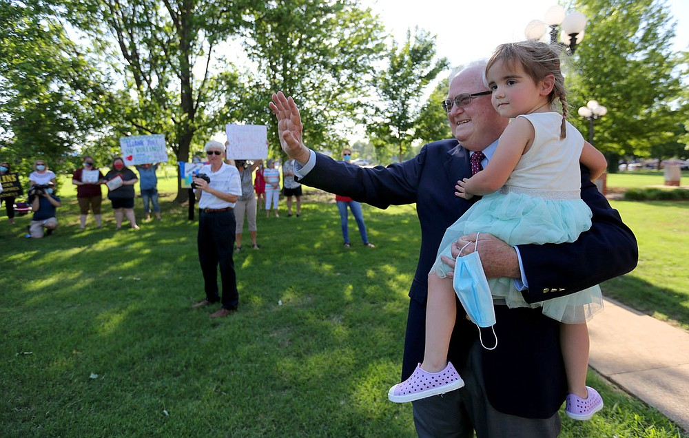 Jim Rollins, superintendent for Springdale Public Schools, holds his granddaughter Adalynn Rollins, 2, as he is greeted by teachers, faculty and well wishers, Tuesday, June 9, 2020, following his last school board meeting in Springdale. Rollins had served as the superintendent for Springdale Public Schools for the last 38 years and has accepted the position as the President of the Northwest Arkansas Technical Institute in Springdale. Visit nwaonline.com/200610Daily/ and nwadg.com/photos for a photo gallery. (NWA Democrat-Gazette/David Gottschalk)