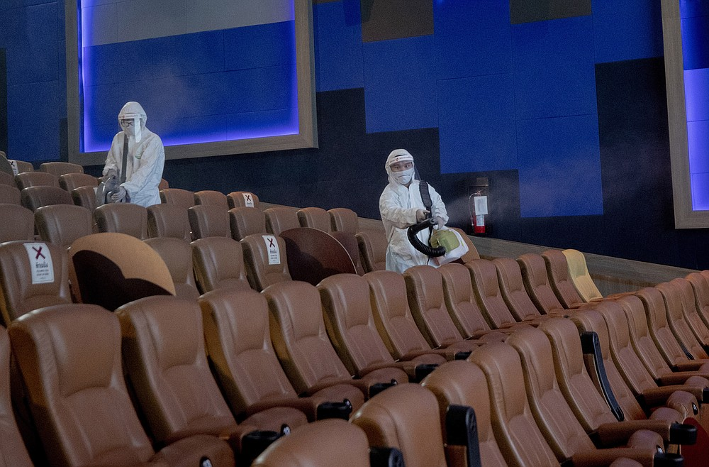 Employees spray disinfectant as a precaution against the coronavirus at the Paragon Cineplex movie theater in Bangkok, Thailand, Monday, June 1, 2020. Thai authorities allowed movie theater and other businesses to reopen, selectively easing restrictions against the coronavirus. (AP Photo/Sakchai Lalit)